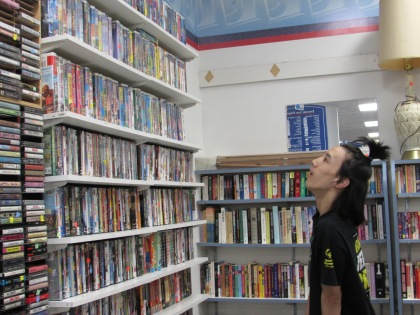 Kelvin looks up at the large collection of movies in the Goodwill East Brunswick store.