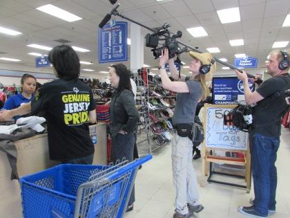 Lara's crew films Kelvin as he pays for his purchases with the $65 his mother awarded him.
